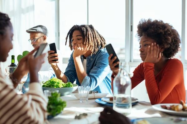 Mensen aan lunchtafel kijkend op smartphone